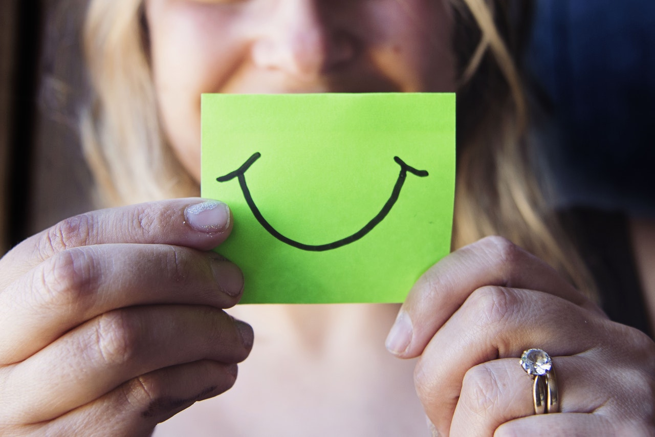 Woman holding a green post it in front of her face with a smile drawn on it to conceal her depression