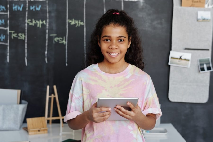 Young teenage girl holding laptop; at-home learning; teen depression