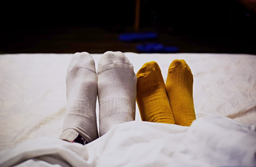 Two different pairs of socks in bed.
