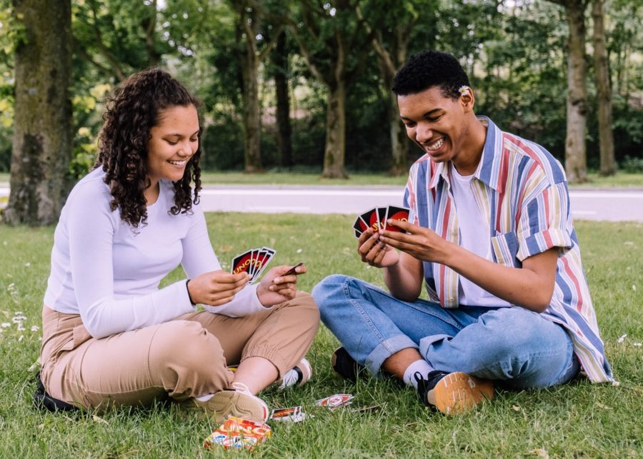 A young man and woman playing Uno outside.