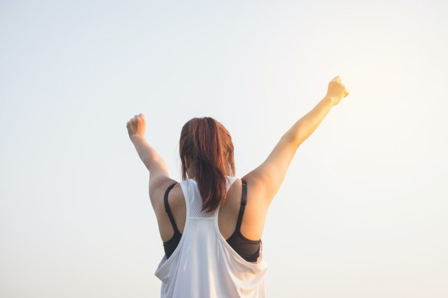Woman facing forward with hands reached to the sky; 10 day mental health challenge.